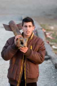 A boy in Sderot playing with rocket fired from Gaza.