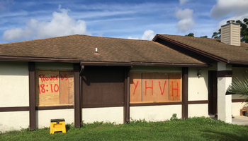 "Home in Florida boarded up against Hurricane Irma with ""YHVH"" and ""Proverbs 18:10"" written on it."